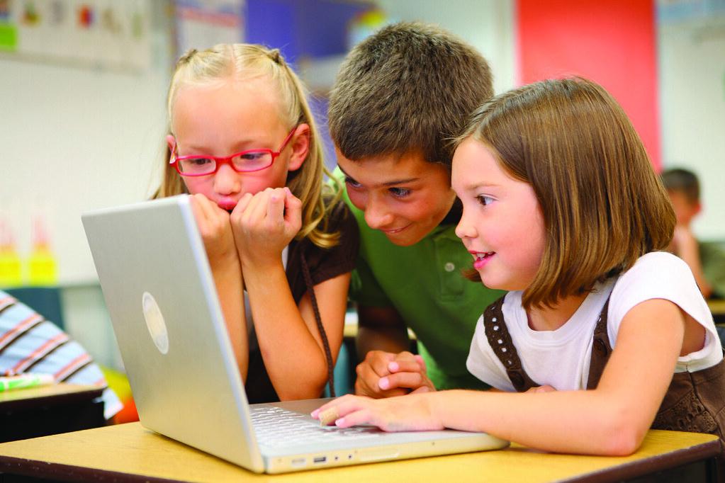 students gathered around laptop