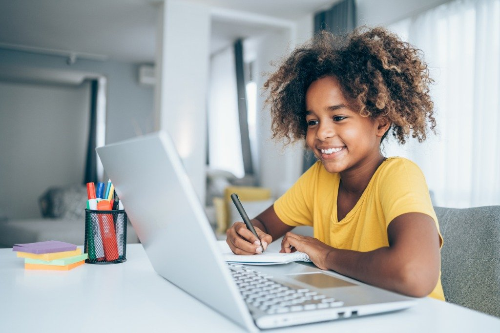 schoolgirl-studying-with-video-online-lesson-at-home-picture-id1285962627